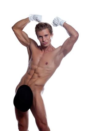 Grinning handsome stripteaser posing in studio